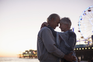 Senior couple hugging on beach at sunset - CAIF17740