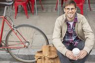 Man drinking coffee on city street - CAIF17755