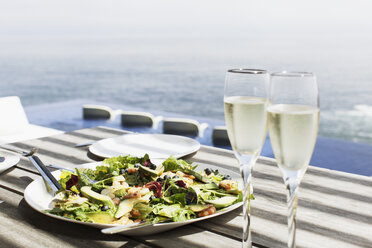 Plate of salad and glasses of champagne on table outdoors - CAIF17944