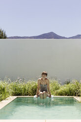 Woman dipping legs in luxury lap pool - CAIF17956