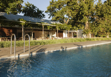 Swimming pool outside luxury house surrounded by trees - CAIF17965