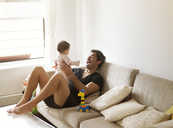 Father playing with daughter while sitting on sofa at home - CAVF09165