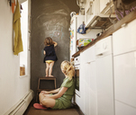 Daughter writing on wall by mother sitting at home - CAVF09186