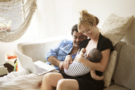 Father looking at woman breast feeding baby girl at home - CAVF09201