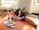 Woman lying on carpet with daughter by food at home - CAVF09204