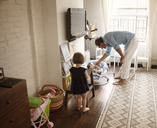Father feeding popsicle to baby girl by daughter standing at home - CAVF09207
