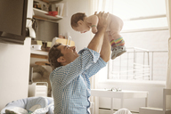 Happy father lifting baby girl at home - CAVF09210