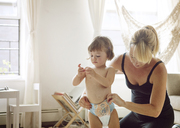 Mother dressing daughter at home - CAVF09213