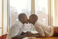 Side view of affectionate couple kissing at table against window home - CAVF09264