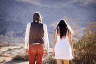 Rear view of couple standing on field - CAVF09324