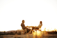 Low angle view of couple sitting on chairs against clear sky - CAVF09336