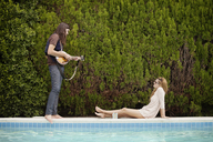 Man playing mandolin while woman sitting by swimming pool - CAVF09372
