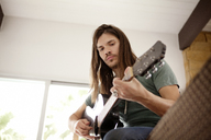 Low angle view of man playing guitar while sitting on sofa at home - CAVF09378