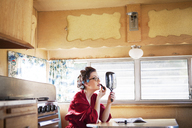 Side view of woman applying lipstick while sitting by table in camper van - CAVF09393