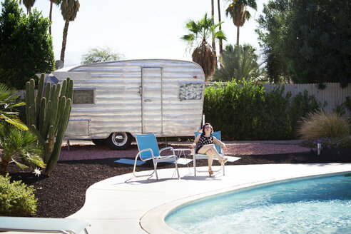 Woman relaxing on chair at poolside against camper van - CAVF09402