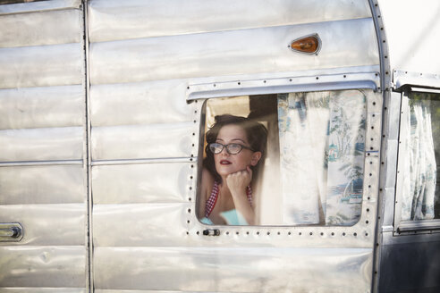Woman with hand on chin looking through window while sitting in camper van - CAVF09408