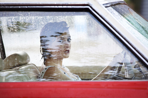 Portrait of woman holding steering wheel while sitting in car - CAVF09420
