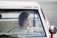 Woman looking through window while sitting in car - CAVF09426
