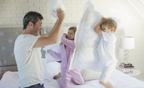 Father and children having pillow fight - CAIF18037