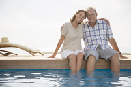 Senior couple dipping feet in swimming pool - CAIF18052