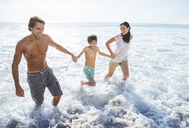Family playing in waves at beach - CAIF18055