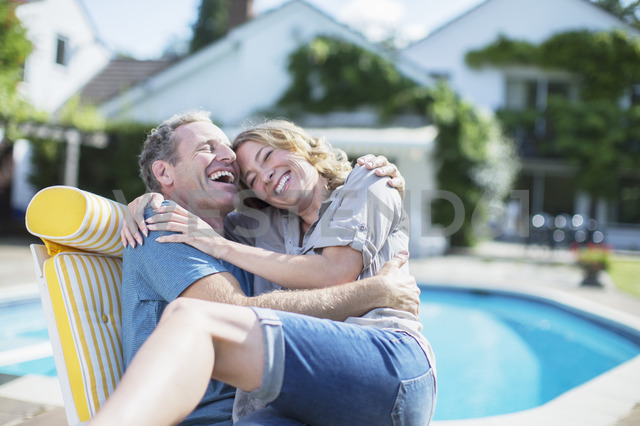 Couple relaxing in lounge chair at poolside - CAIF18103
