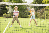 Children playing tennis on grass court - CAIF18121