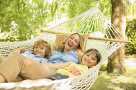 Mother and children relaxing in hammock - CAIF18124