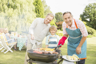 Multi-generation men grilling meat and corn at barbecue in backyard - CAIF18133