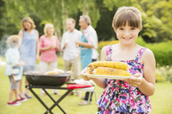Smiling girl holding grilled corn in backyard - CAIF18136
