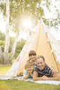 Father and children relaxing in teepee in backyard - CAIF18142
