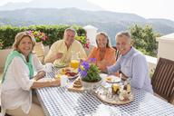 Senior couples enjoying breakfast on patio - CAIF18271