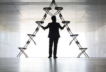 Businessman arranging office chair installation art - CAIF18286