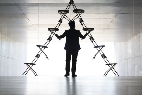 Businessman arranging office chair installation art - CAIF18286