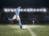 Soccer player kicking ball on field - CAIF18316