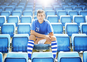 Soccer player sitting in empty stadium - CAIF18328