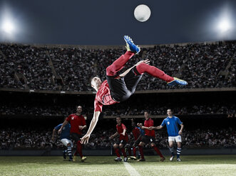 Soccer player kicking ball on field - CAIF18346