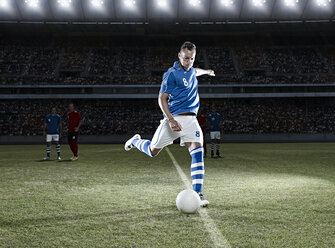 Soccer player kicking ball on field - CAIF18349