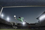 Goalie jumping for ball in soccer net - CAIF18364