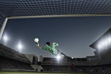 Goalie jumping for ball in soccer net - CAIF18364