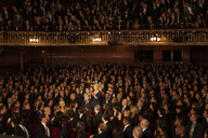 Spotlight on audience member clapping in theater - CAIF18400