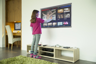 Girl using touch screen television in living room - CAIF18430