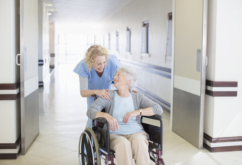 Nurse with aging patient in wheelchair in hospital corridor - CAIF18530