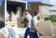 Movers carrying cardboard boxes in driveway - CAIF18551