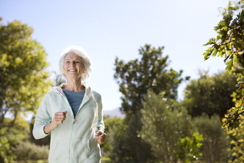 Senior woman running in park - CAIF18608