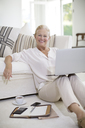 Senior woman using laptop on living room floor - CAIF18611