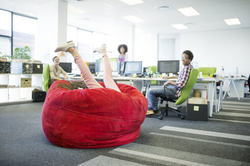 Businesswoman playing in beanbag chair in office - CAIF18617