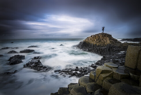 United Kingdom, Northern Ireland, person on rock at Giant's Causeway - STCF00412