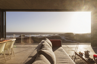 Modern living room overlooking ocean - CAIF18779