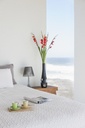 Breakfast tray on bed in modern bedroom with ocean view - CAIF18788